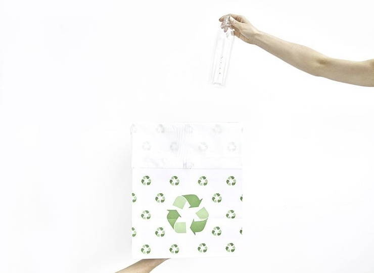 Person putting empty bottle of chlorophyll water into recycling bag