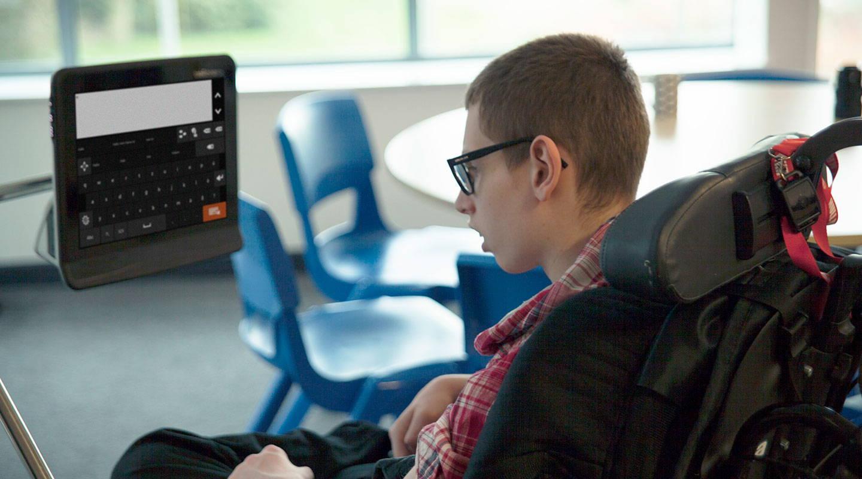 """Junger Mann benutzt die UK-App """"Communicator 5"""" auf seinem augengesteuerten Gerät von Tobii Dynavox"""
