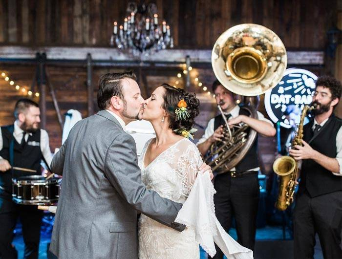 Bride and groom kissing in front of band at wedding reception