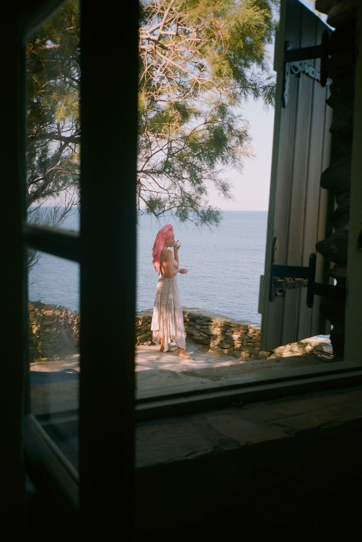 girl on greek island ocean boho standing by cliff