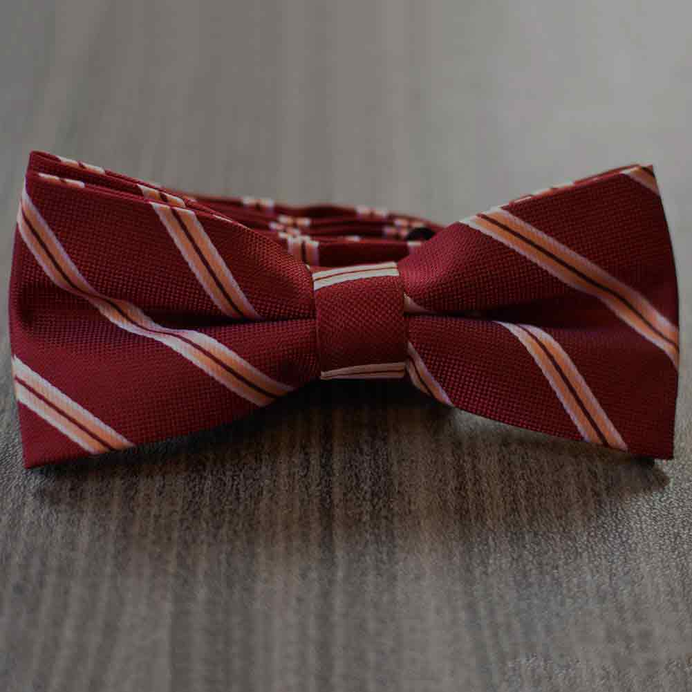 Burgundy bow tie with coral stripes on a wood floor