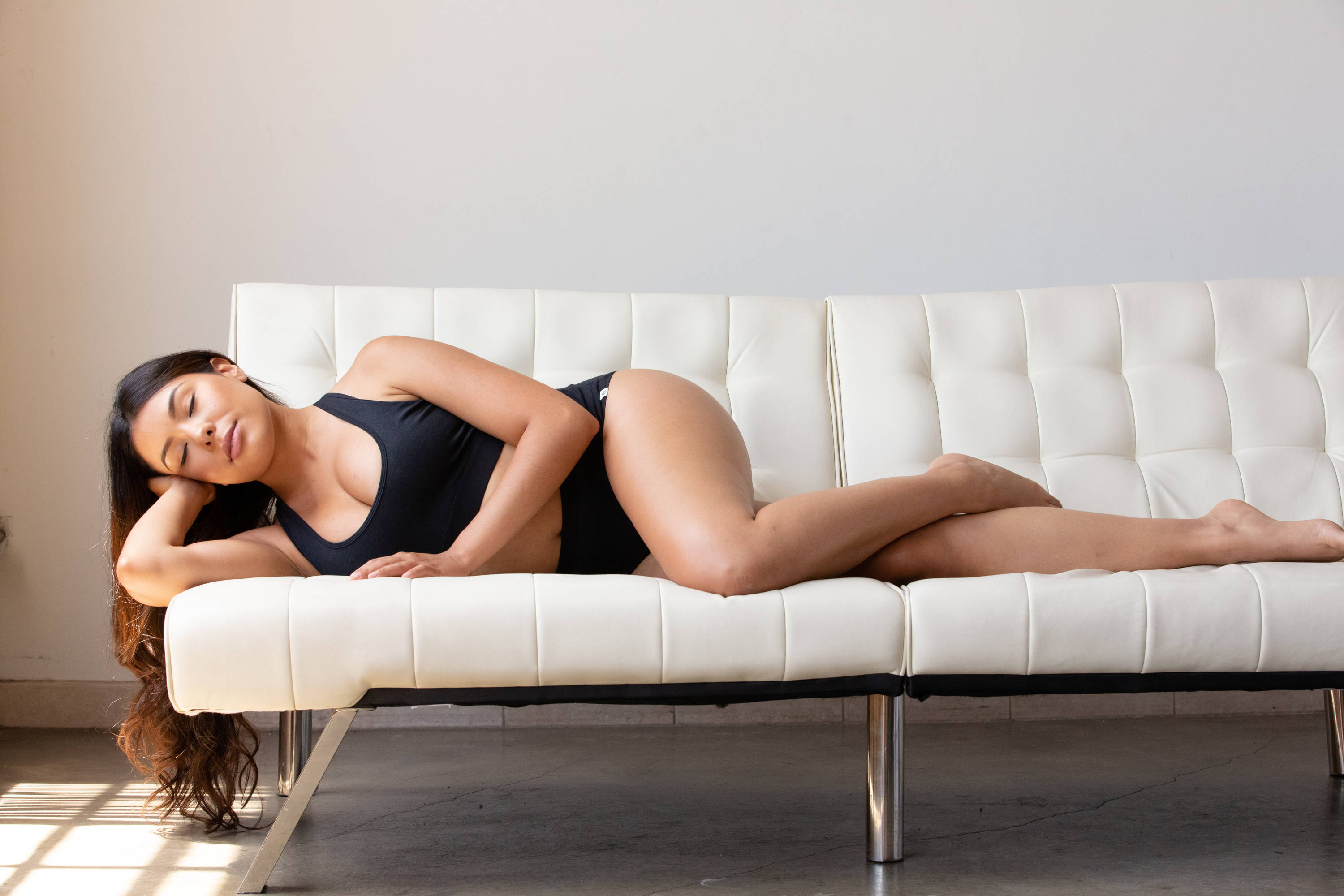 A woman in WAMA hemp racerback bralette and high waisted underwear sleeps on a white sofa.