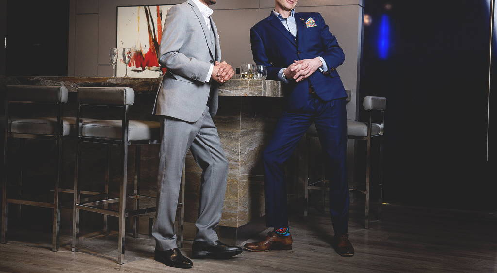 Two dapper men in Canadian made bespoke suits lean against a bar