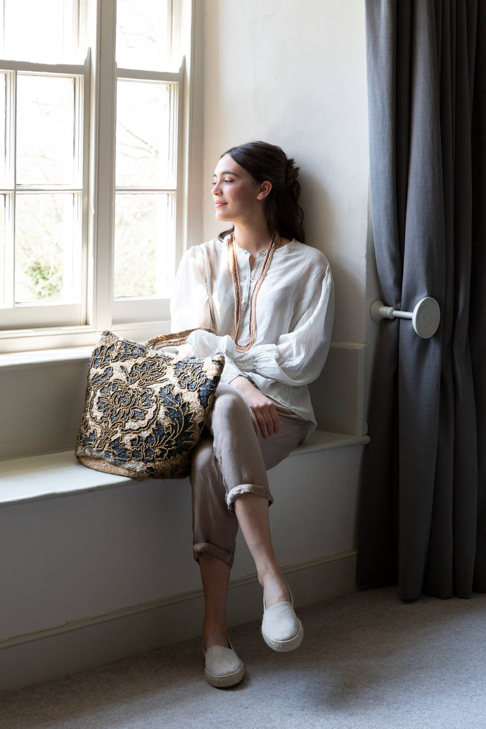 Seated model wearing neutral trousers and white blouse.