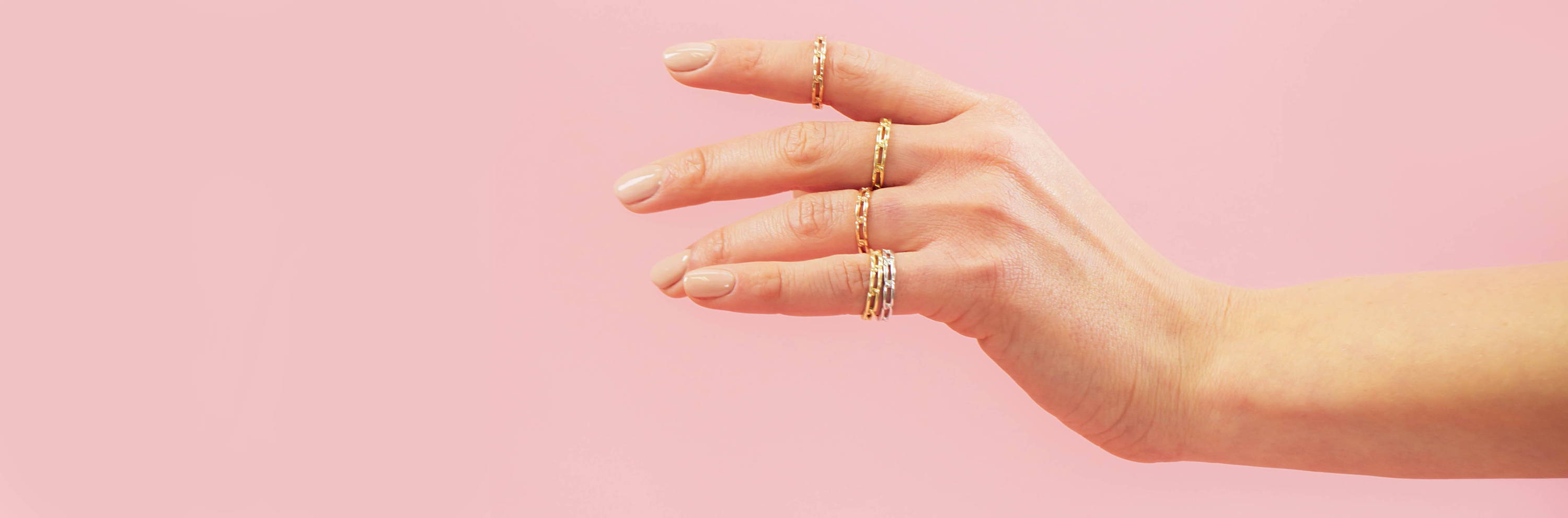 Close up of hand wearing Maya Brenner link rings against a pink background.