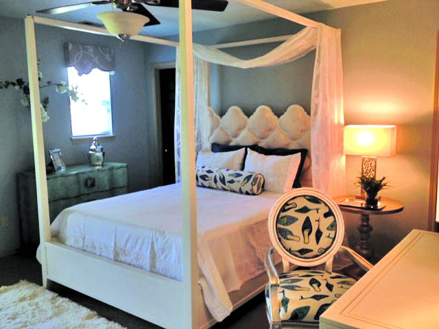 white upholstered poster bed next to chair in front of white vanity