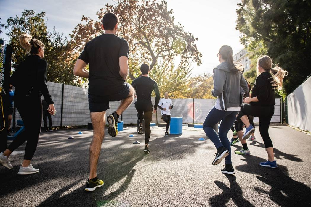 Group Of People Exercising Outside In The Sun