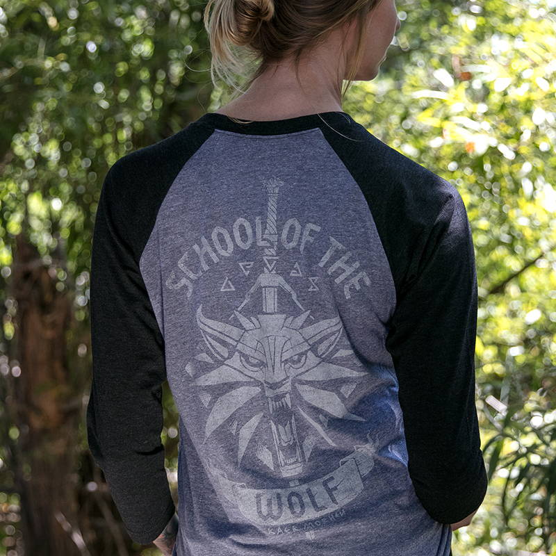 Photo of a female model wearing a Witcher raglan shirt, showing a Wolf School design