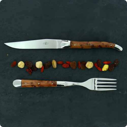 Laguiole table knife and fork on a slate  with red yellow and black dried fruits