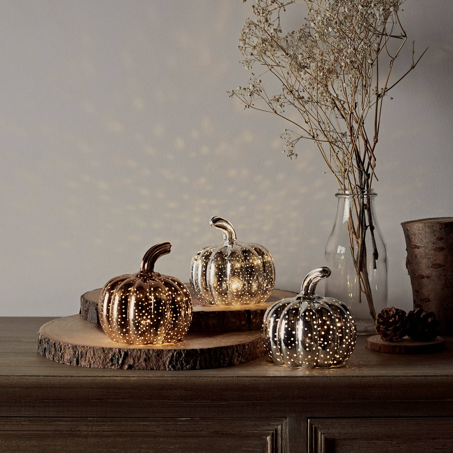 Mottled pumpkin trio illuminated on table styled at different heights