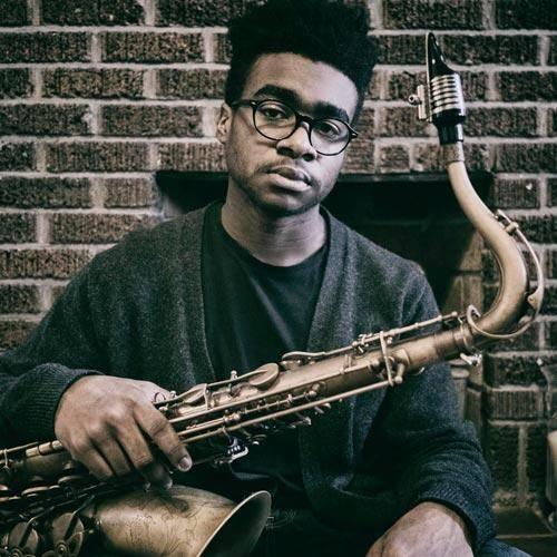 Sax player Morgan Guerin holding a P Mauriat tenor sax