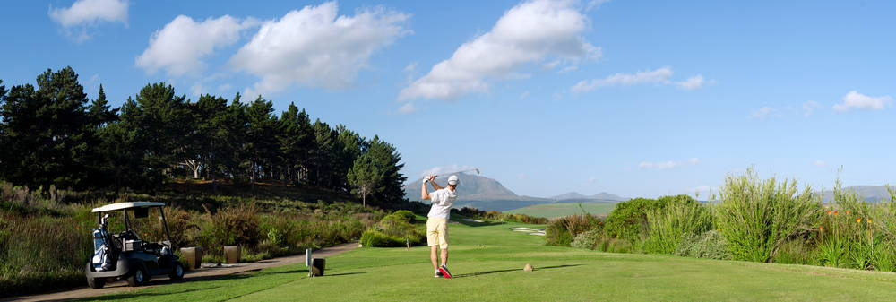 Golfer with golf cart swinging on a golf course with mountains in the distance