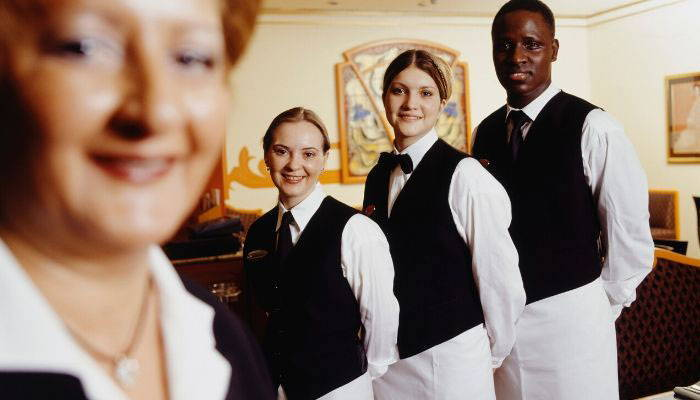 Restaurant waiters wearing black bow ties and vests