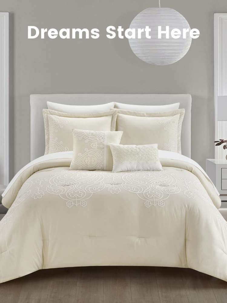 A bed with a beige comforter set on top of it