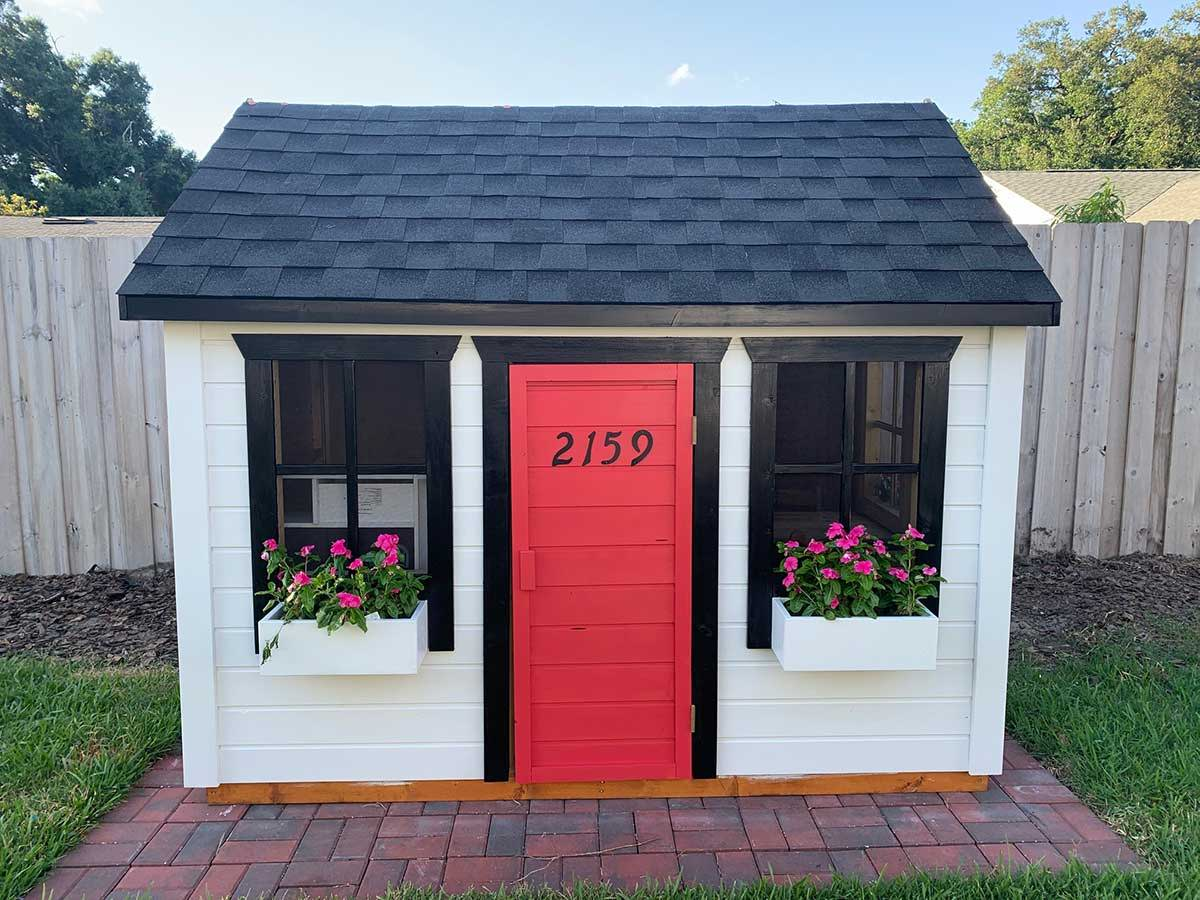 Wooden playhouse with a black roof and white flower boxes with pink flowers by WholeWoodPlayhouses