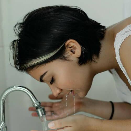 Junge Frau wäscht Gesicht mit lauwarmem Wasser