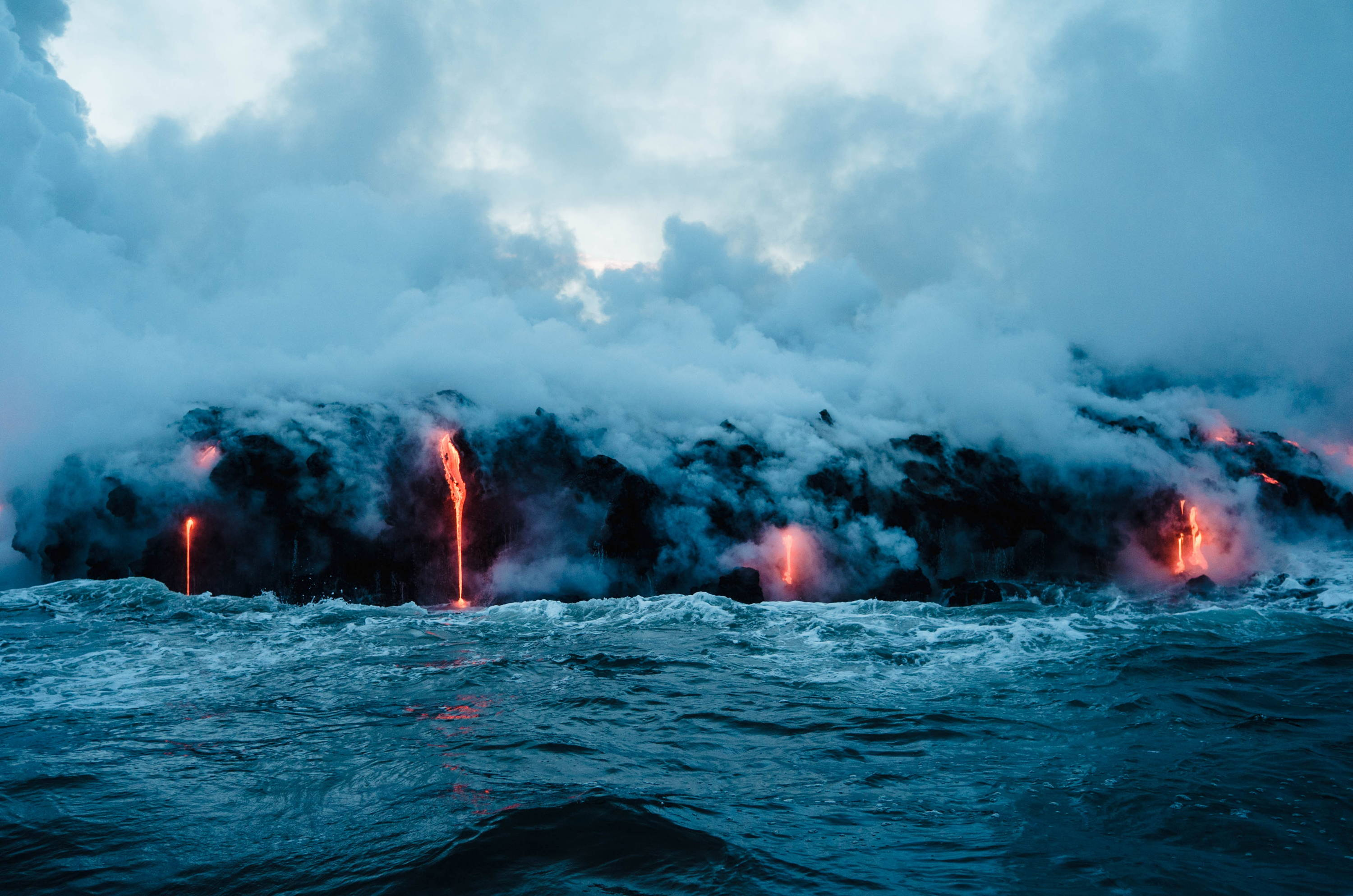 Hawaii Volcano Story: Kilauea and Hawaii Volcanoes National Park. Lava flows over the cliff's edge and into the ocean on the Big Island in Hawaii.