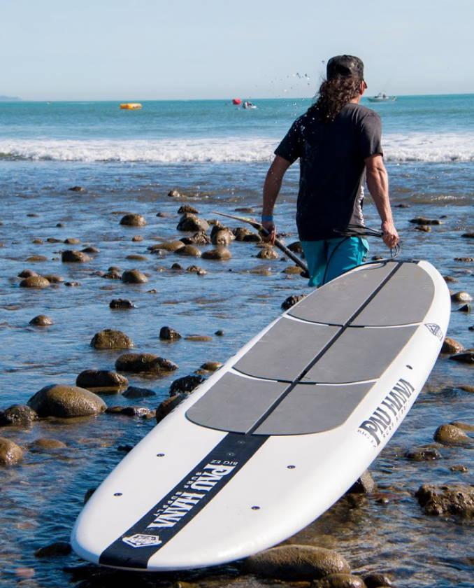 Todd carrying Pau Hana Ricochet Doheney State Beach Park in Dana Point California over rocks