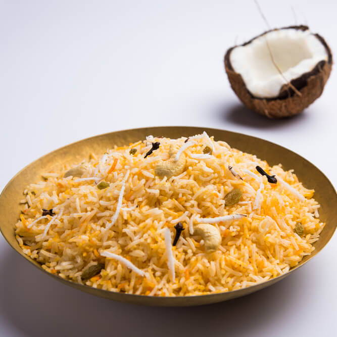 a bowl of golden rice with cardamom and a coconut half in the background