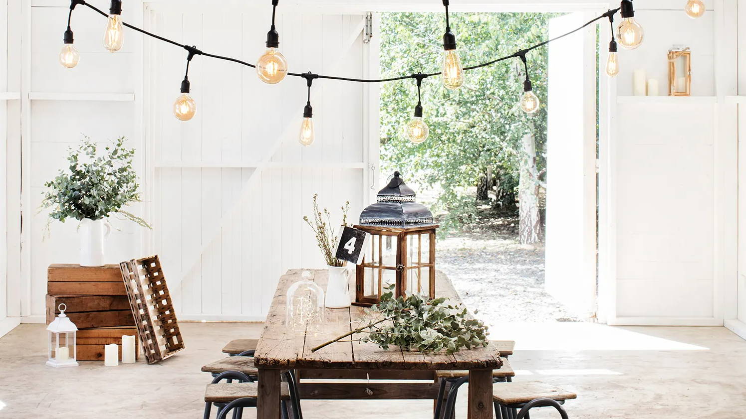 Barn setting with wooden lantern placed on table with green foliage and candles