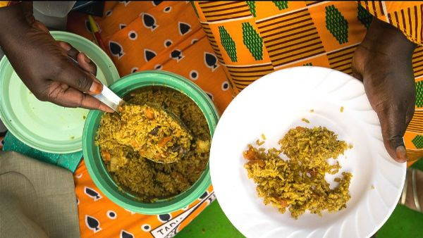 pilau african rice in a green pot being served on a plate by a woman in colorful organge pattern