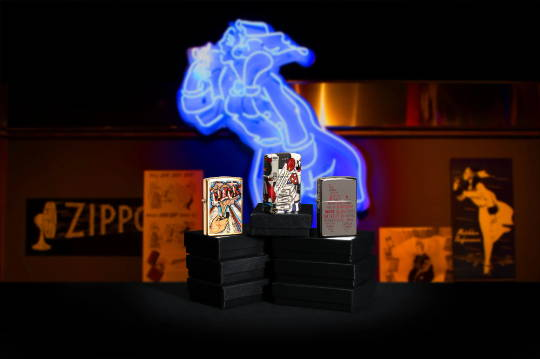 Zippo Click lighter, Zippo I Spy lighter, and Zippo Flame lighter standing on a stack of lighter boxes with a neon Windy sign and Zippo posters in the background.
