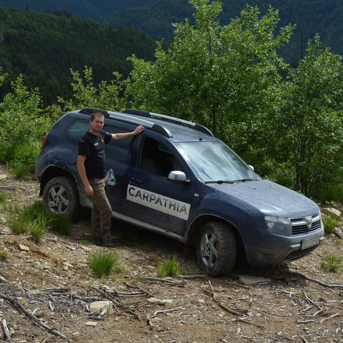 A forest ranger stands next to his car in nature