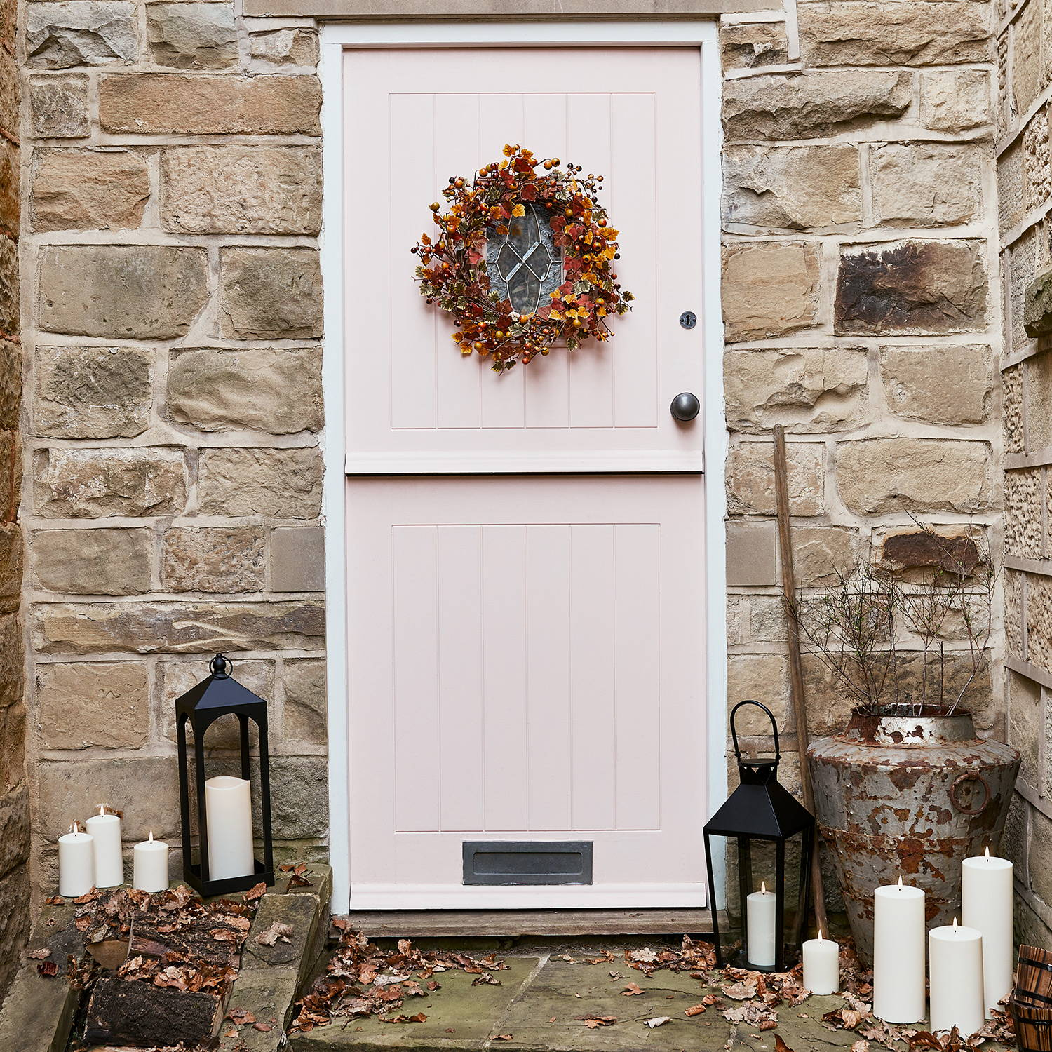 Front door setting featuring harvest autumn wreath, lanterns and LED candles