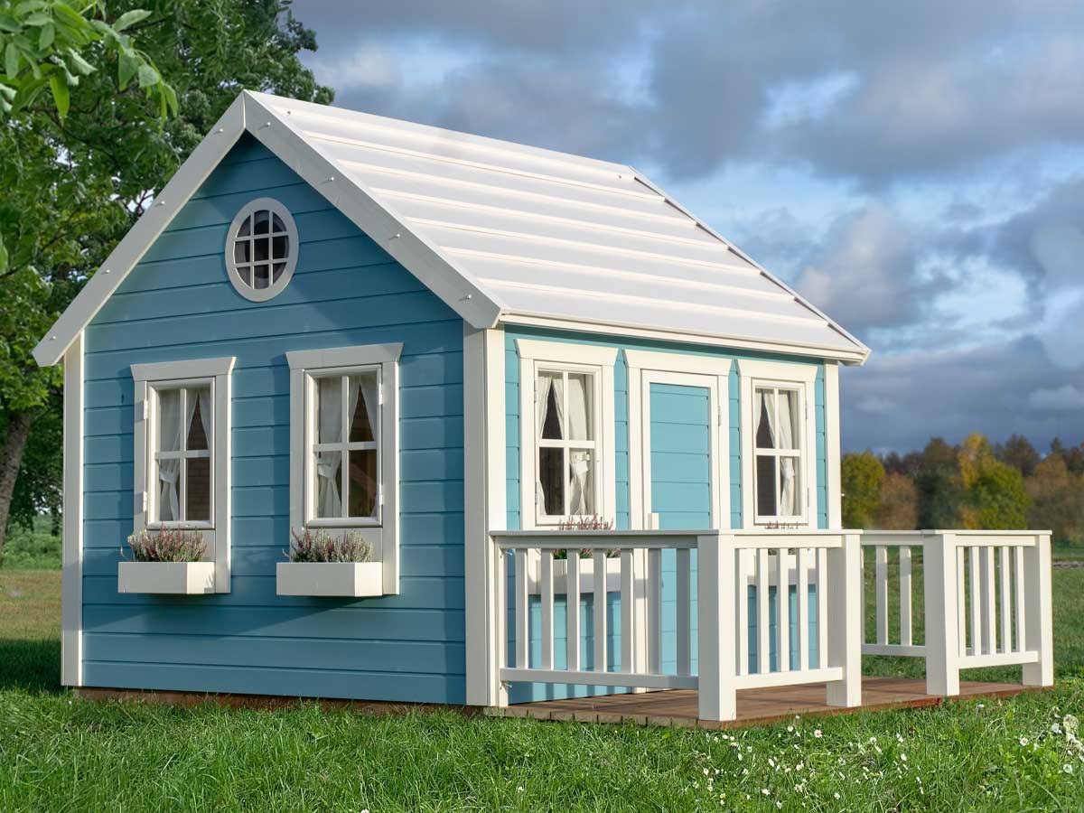 Wooden Playhouse in blue colour with a white terrace in a green backyard by WholeWoodPlayhouses
