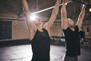 Mann und Frau hängen an Stange zur Vorbereitung auf Klimmzüge
