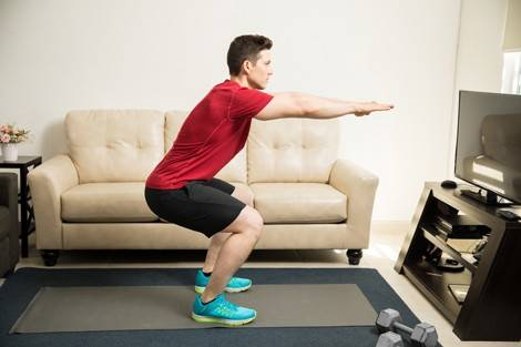 Mann macht Squats als Teil seines Krafttrainings zu Hause