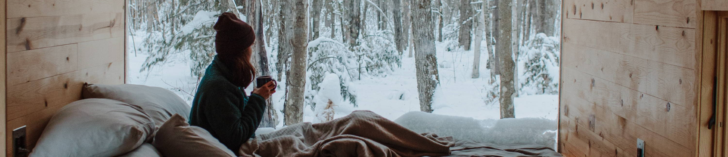 woman sipping coffee in bed looking at snow