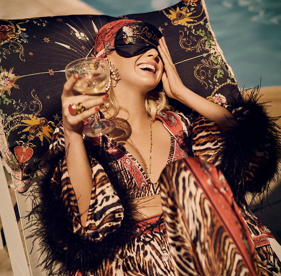 Nadia Fairfax in CAMILLA leopard print on pillow wearing eye mask