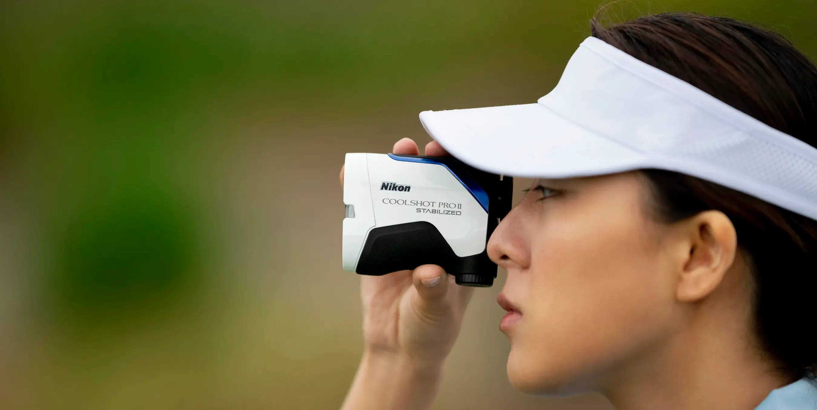 Golfer using her COOLSHOT PROII STABILIZED rangefinder on the course