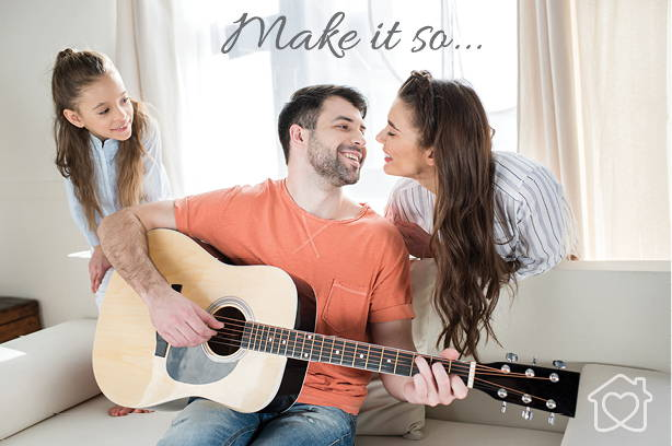 man with family playing guitar in lounge room about to kiss wife
