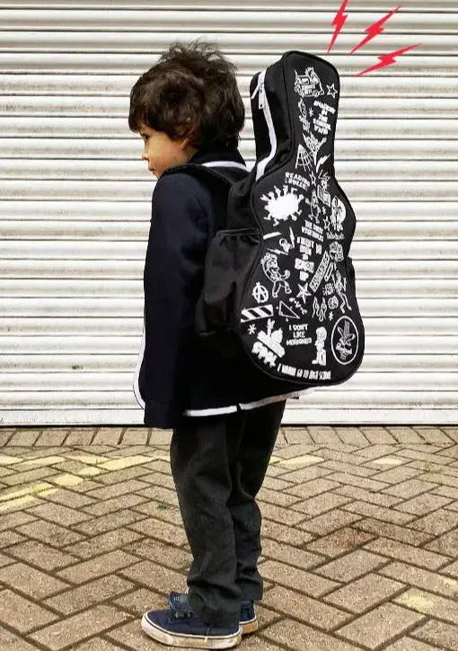 Young boy wearing a black outfit and black guitar shaped backpack