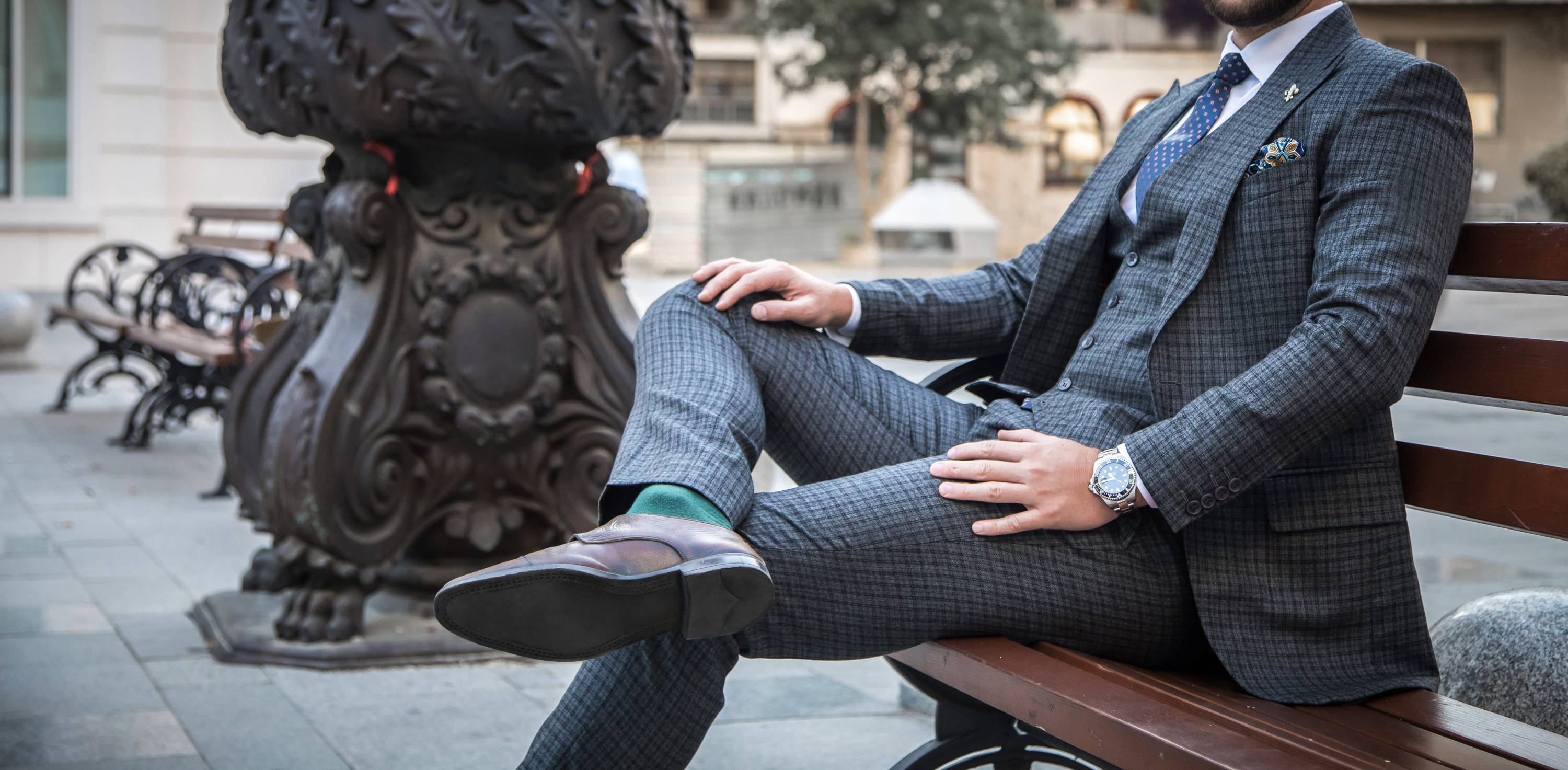 Dapper gentleman sits on a bench in a grey checked suit with luxury watch, tie and pocket square