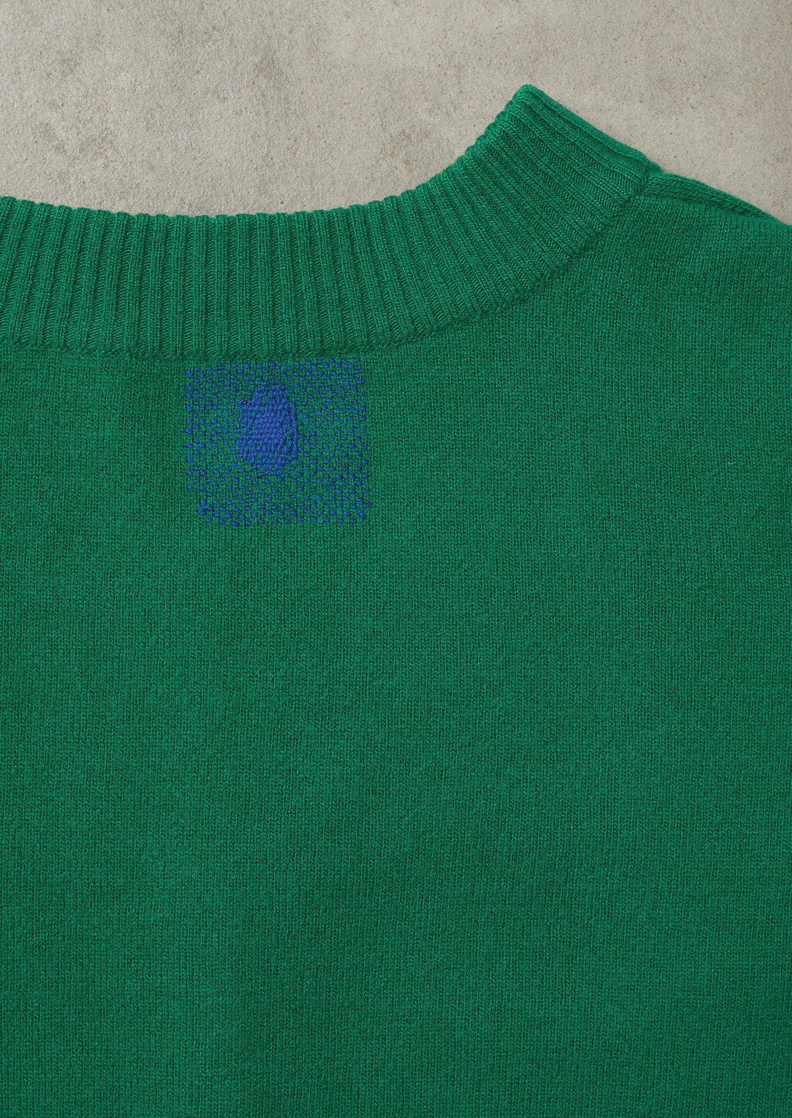 Green sweater from TOAST with mended hole.