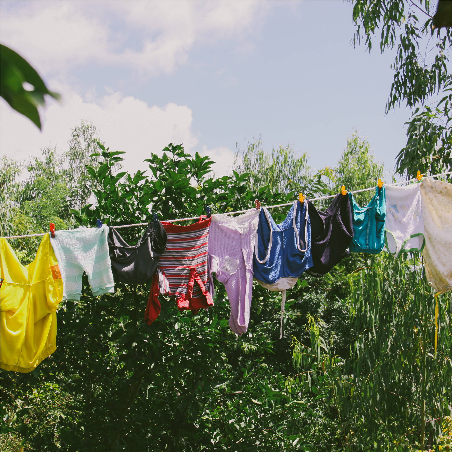 Clothes of all different colors hang on a drying line in front of thick green vegetation in Nicaragua.
