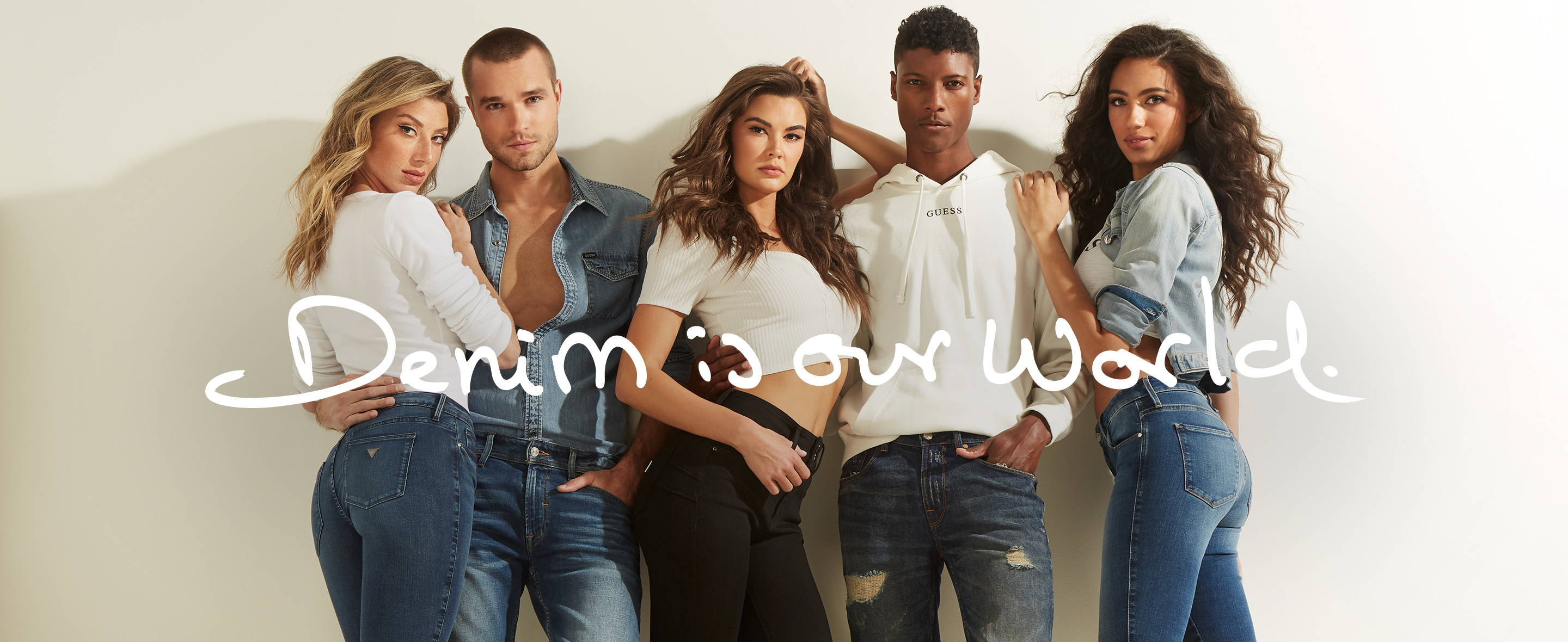 a group of people wearing GUESS denim jeans and tops