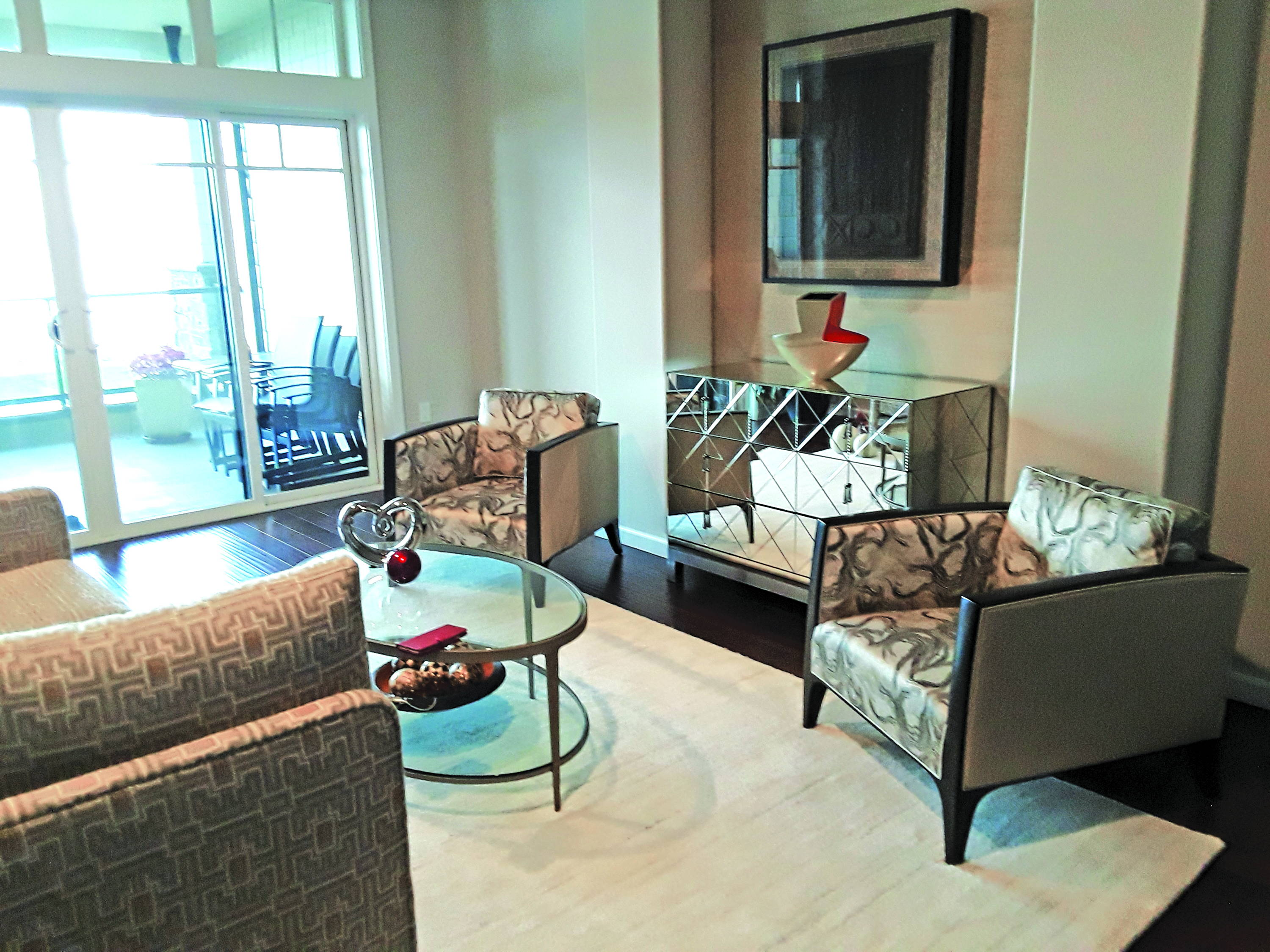 two patterned fabric arm chairs in front of glass coffee table on beige rug