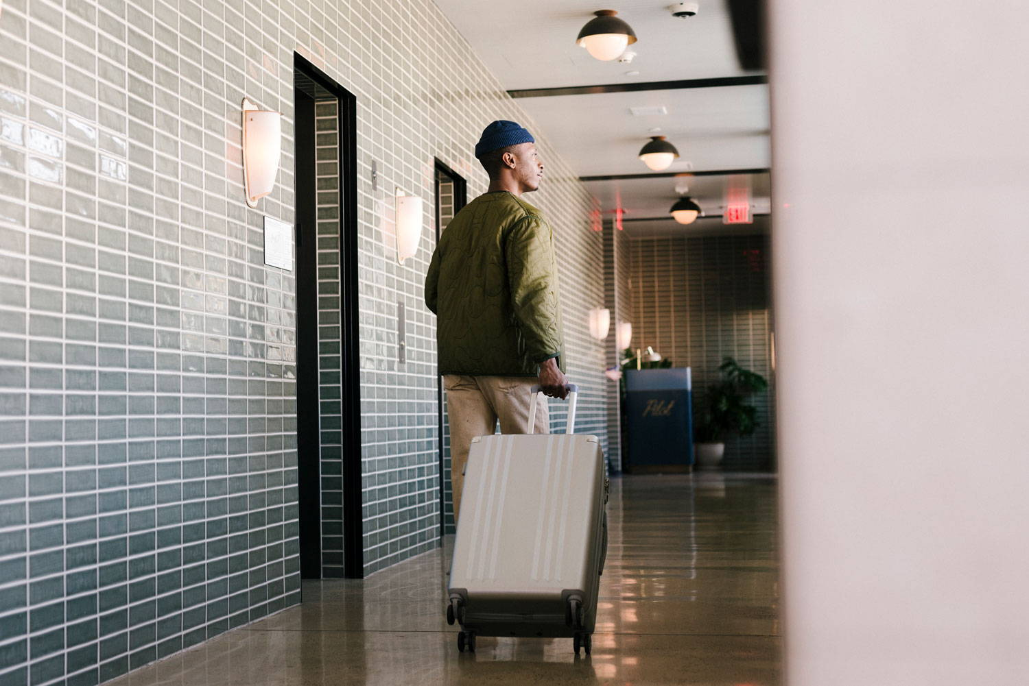Male Model with the Ambeur Carry-on in Silver walking through hallway