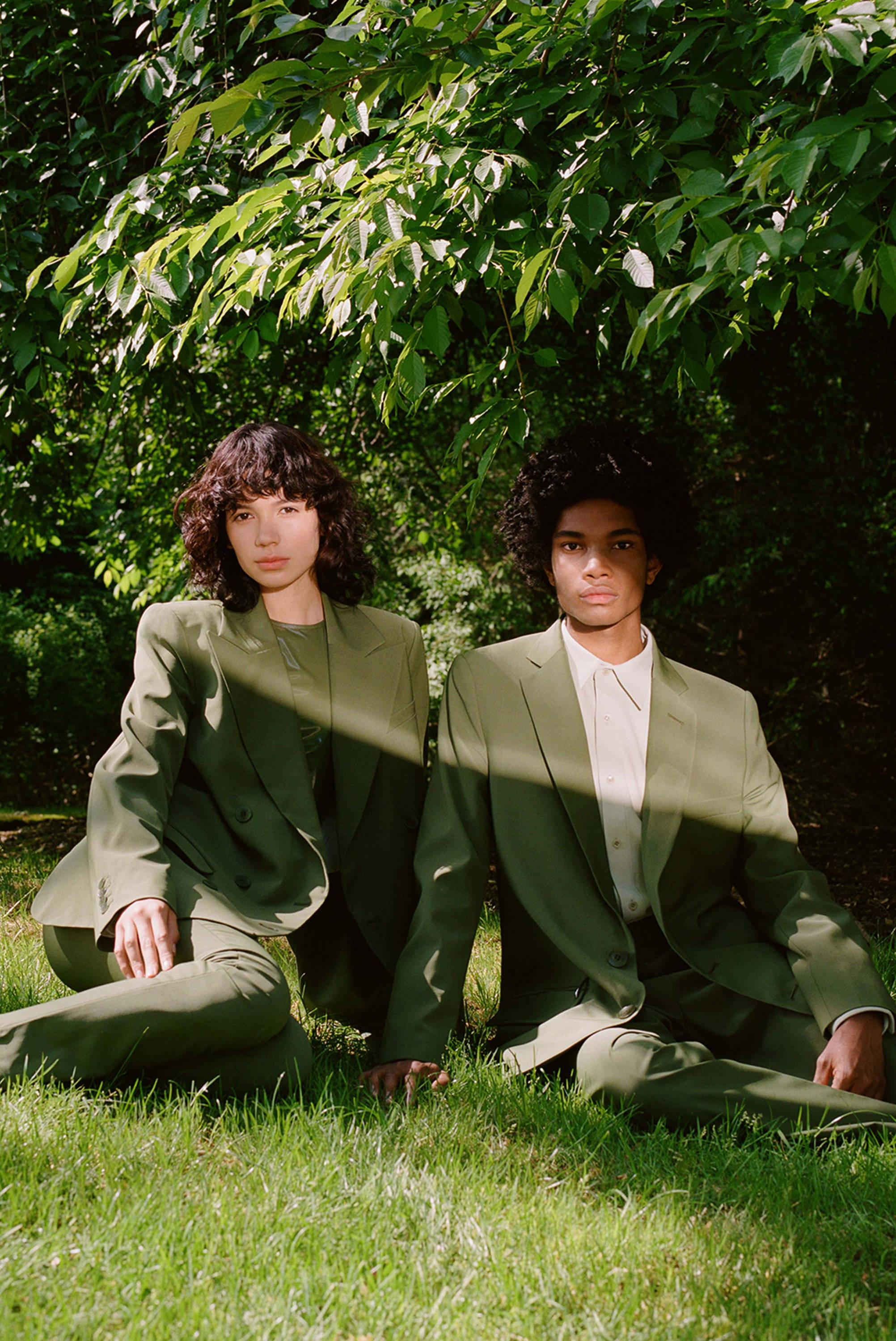 Two models sitting under a tree. Both models are wearing green suits.