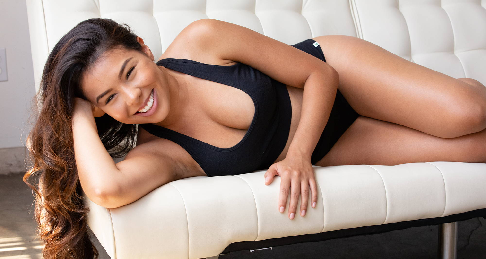 Woman lying on the couch wearing affordable ethical clothing from WAMA Underwear.