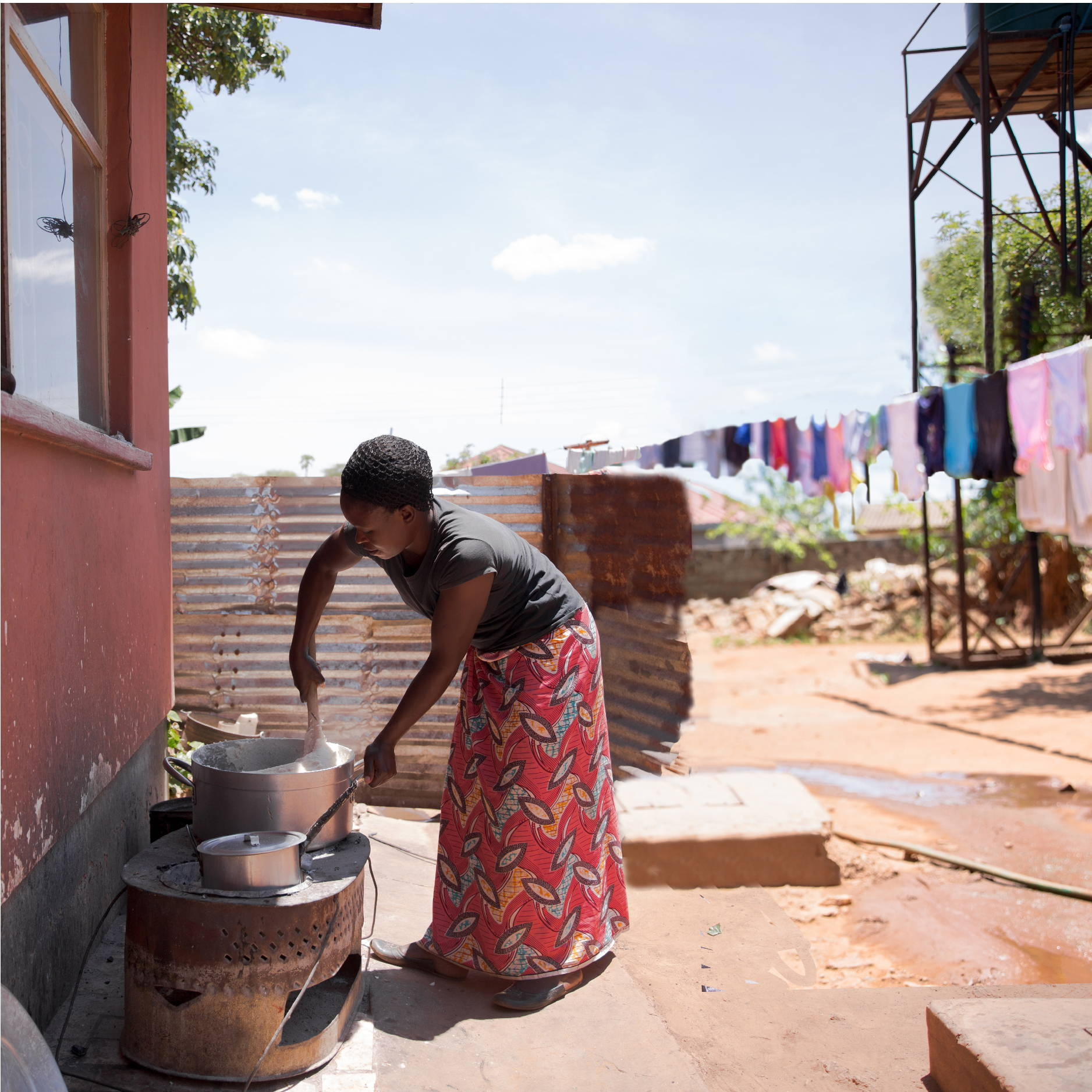 A Zambian woman stands outside cooking and stirring a large pot of nshima for small children.