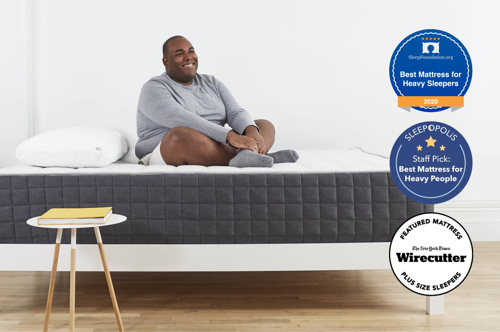 Man sitting on Helix Plus mattress with awards presented to mattress featured on the image