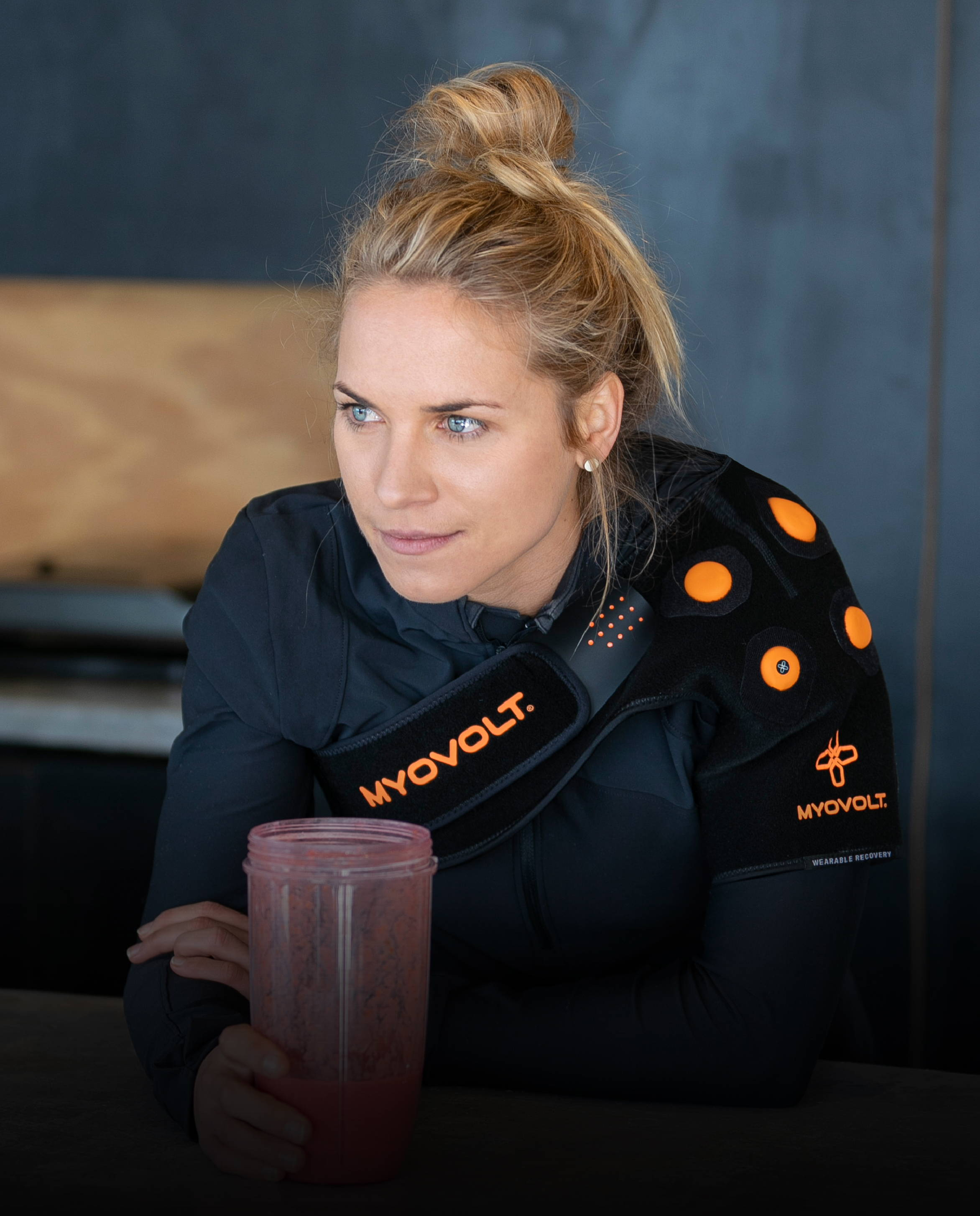 Dr Hannah Wells wearing Myovolt Shoulder with a smoothie in the kitchen