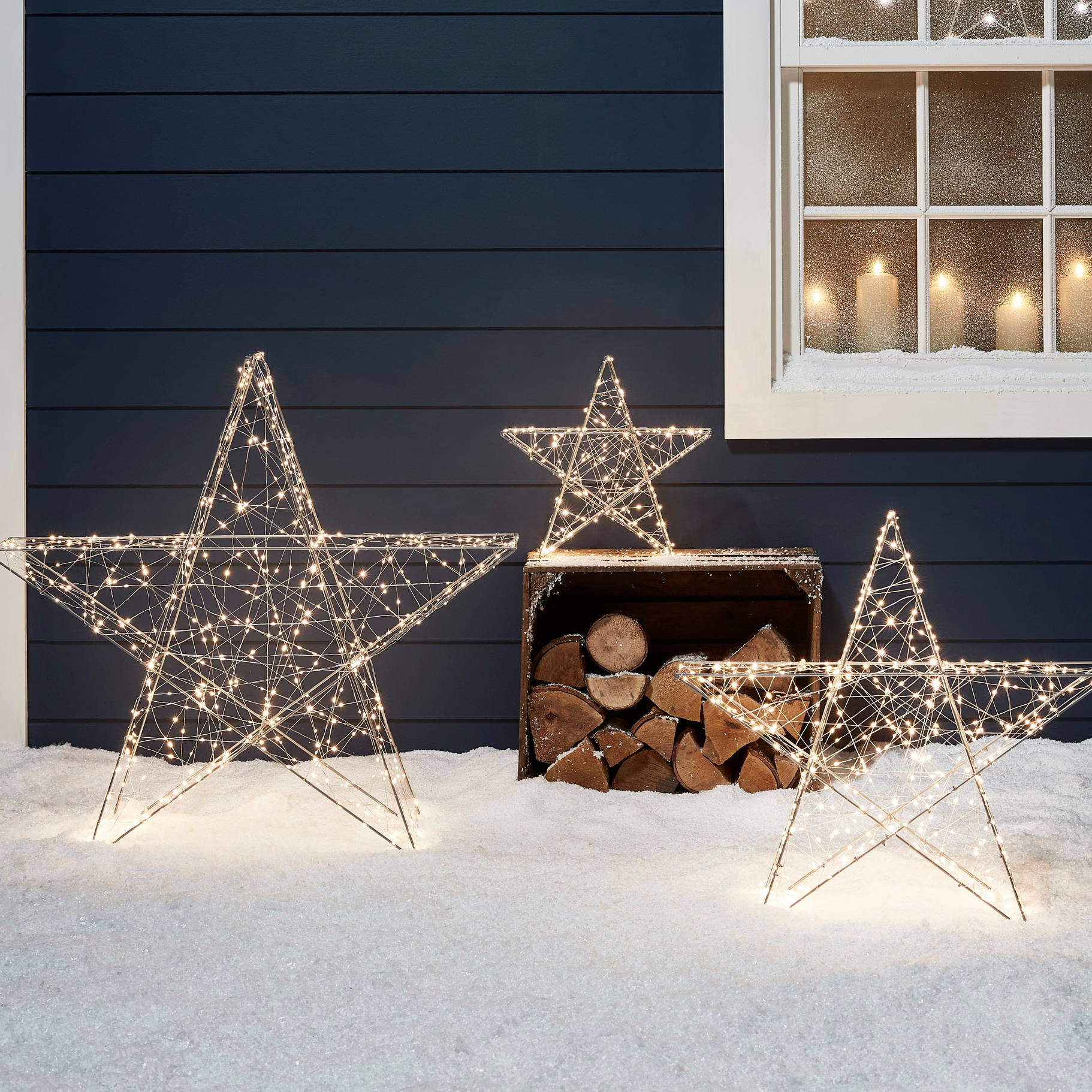 Warm White Star Decorations stood outside a home