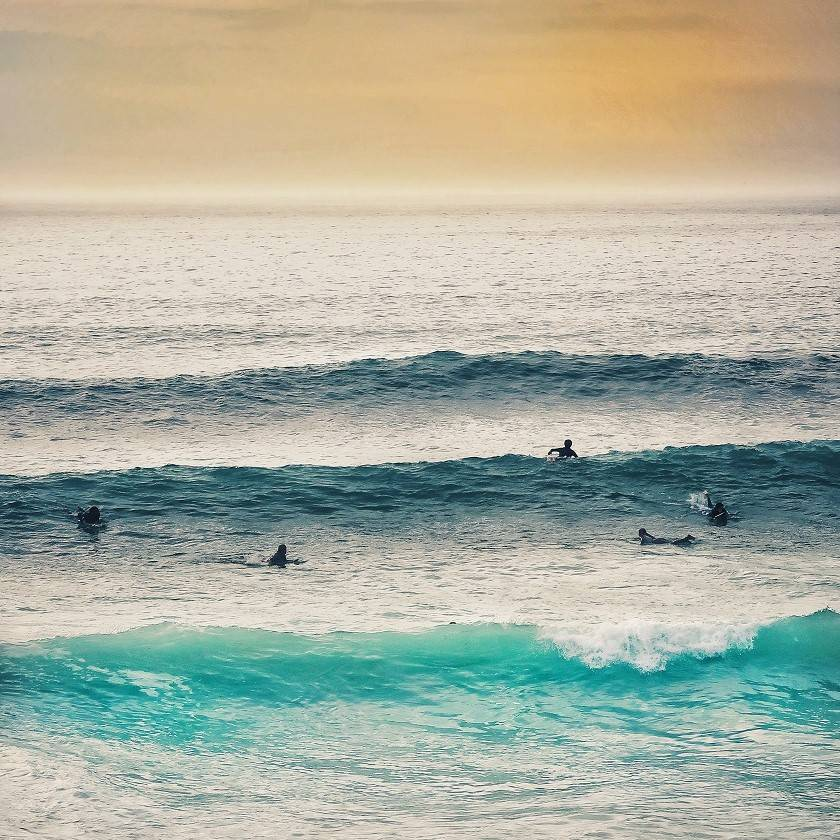Surfers in the line up at sunset