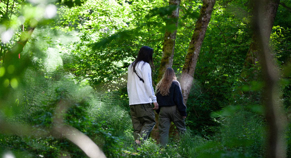 Two people wearing it Vanishes clothing walking in the forest.